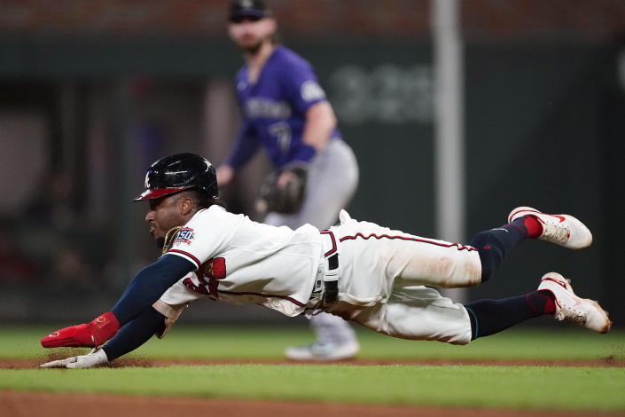 Atlanta Braves second baseman Ozzie Albies (1) slides into second before being tagged out in the fifth inning of a baseball game against the Colorado Rockies Tuesday, Sept. 14, 2021, in Atlanta. (AP Photo/John Bazemore)