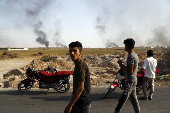 People in Akcakale, Sanliurfa province, southeastern Turkey, at the border with Syria, watch smoke billowing from targets inside Syria, during bombardment by Turkish forces, Oct. 10, 2019. (Photo: Lefteris Pitarakis/AP )