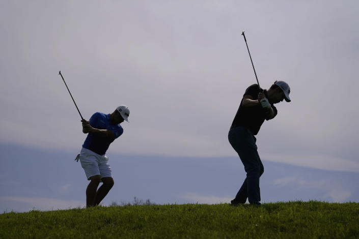 Patrick Cantlay, right, and Gary Woodland chip on the 12th green during a practice round of the U.S. Open Golf Championship, Wednesday, June 16, 2021, at Torrey Pines Golf Course in San Diego. (AP Photo/Jae C. Hong)