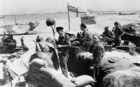 British troops make their way through low water and up the beach after leaving landing craft which transported them across the Channel to the Normandy beachhead - Credit: BRITISH OFFICIAL PHOTO