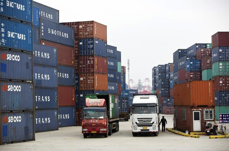 Trucks carrying containers drive at a port of Shanghai Free Trade Zone