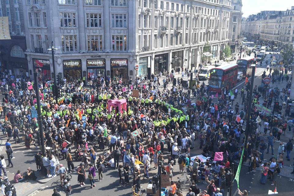 Police officers ring climate activists from the Extinction Rebellion group who are gathered around a pink structure they built in the middle of Oxford Circus in central London on August 25. (Getty)