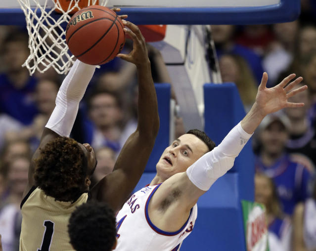 Wofford forward Chevez Goodwin (1) rebounds against Kansas forward Mitch Lightfoot (44) during the first half of an NCAA college basketball game in Lawrence, Kan., Tuesday, Dec. 4, 2018. (AP Photo/Orlin Wagner)