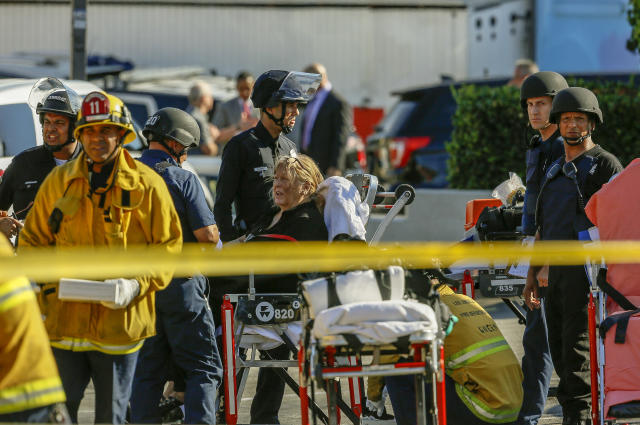 <p>An unidentified woman is helped by paramedics at a triage area after a gunman barricaded himself inside a Trader Joe's store in Los Angeles on Saturday. (Photo: Damian Dovarganes/AP) </p>
