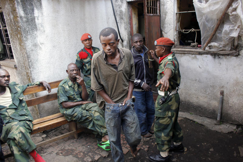 In this photograph taken Friday Aug. 10, 2012, Ibrahim Nsanzimana, a 28-year-old Rwandan man, is led out of his overcrowded jail at the Congolese military intelligence offices in Goma, eastern Congo. Out of work and desperate to make a living, Nsanzimana agreed to join the Rwandan army in early July. After spending a week learning how to shoot with AK-47 assault rifles, he was told he was going to fight to take North Kivu province (of eastern Congo) and to make it part of Rwanda. Nsanzimana was captured three weeks ago by Congolese Tutsi soldiers. (AP Photo/Jerome Delay)