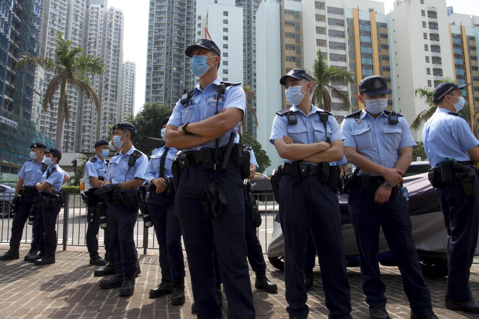 Police officers stand guard as many supporters queue up outside a court to try to get in for a hearing in Hong Kong Monday, March 1, 2021. Pro-democracy activists detained by police on Sunday on charges of conspiracy to commit subversion under the sweeping national security law, are expected to appear in court. (AP Photo/Vincent Yu)