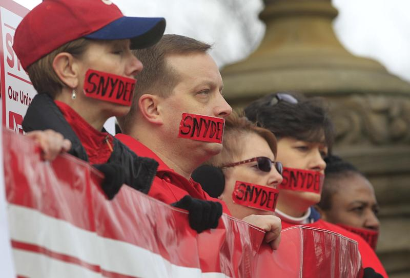 About a dozen members of the Michigan Nurses Association stand on the state Capitol steps in Lansing, Mich., Monday, Dec. 10, 2012,  protesting right-to-work legislation. Organizers say the gathering was meant to symbolize the silencing of unions that nurses say will happen should the legislation become law.(AP Photo/Carlos Osorio)