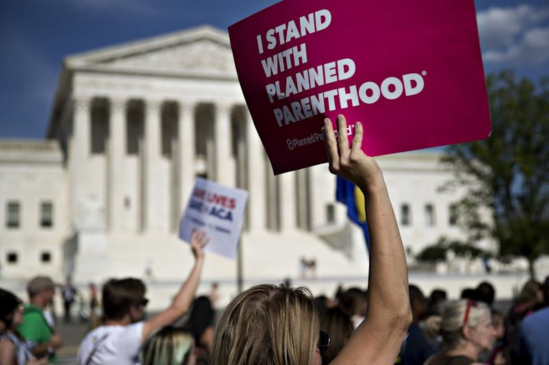 """A demonstrator holds a sign that reads """"I Stand With Planned Parenthood"""" near the U.S. Supreme Court in Washington on June 28, 2017."""