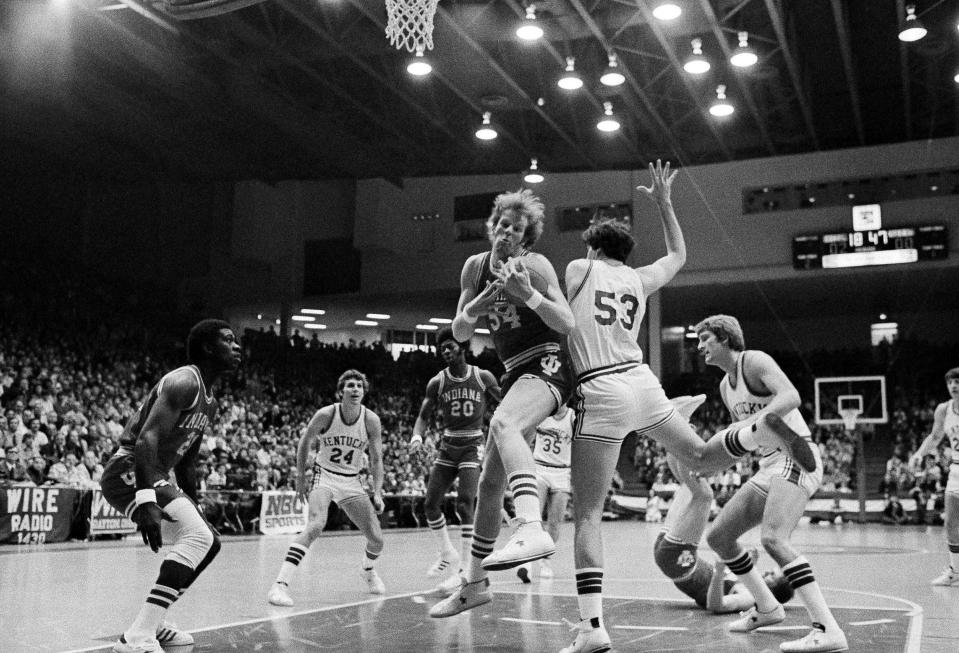FILE - Indiana's Kent Benson (54) takes a rebound away from Kentucky's Rick Robey (53) during an NCAA college basketball at a Mideast Regional championship game at the University of Dayton arena in Dayton, Ohio, in this March 22, 1975, file photo. Kentucky's Bob Guyette is at right. Minutes after losing 92-90 to archrival Kentucky in the Mideast Regional championship, the underclassmen vowed to come back the next season and go undefeated. They did. And 45 years later, the 1975-76 Hoosiers remain America's last perfect college basketball team. (AP Photo/Charles Knoblock, File)