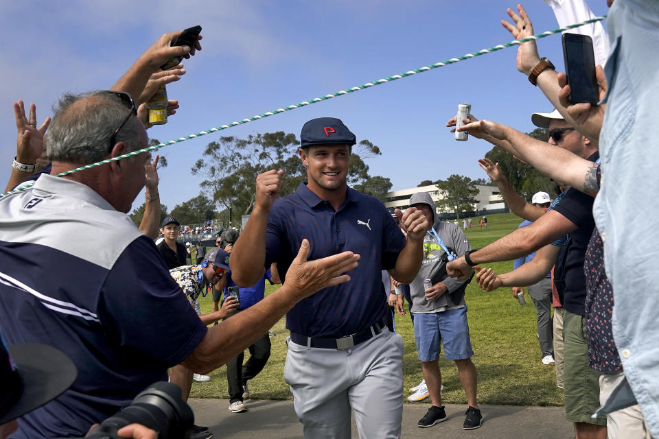 Bryson DeChambeau greets fans as he walks to the 16th tee during the third round of the U.S. Open Golf Championship, Saturday, June 19, 2021, at Torrey Pines Golf Course in San Diego. (AP Photo/Gregory Bull)