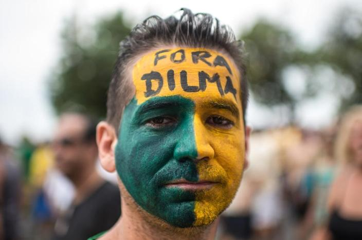"""A demonstrator with his face painted in the colours of the Brazilian national flag and a message reading """"Dilma out"""" takes part in a rally to protest against the government in Rio de Janeiro on March 15, 2015 (AFP Photo/Christophe Simon)"""