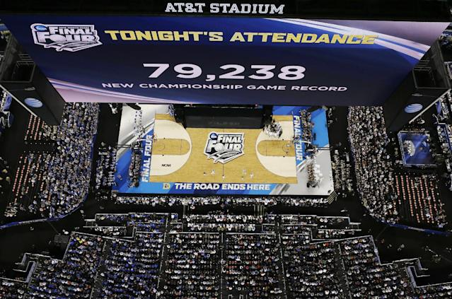 The big screen shows the number of people in attendance during the second half of the NCAA Final Four tournament college basketball championship game between Connecticut and Kentucky Monday, April 7, 2014, in Arlington, Texas. (AP Photo/David J. Phillip)