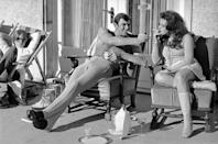 <p>George Lazenby offers co-star Helena Ronee a light, while filming On Her Majesty's Secret Service.</p>