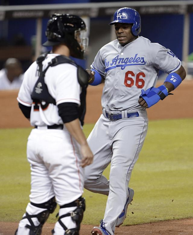 Los Angeles Dodgers' Yasiel Puig (66) scores on a double by Hanley Ramirez in the fourth inning as Miami Marlins catcher Koyie Hill, left, watches during a baseball game, Wednesday, Aug. 21, 2013 in Miami. (AP Photo/Lynne Sladky)