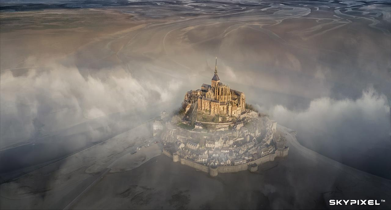 "<p>Mont Saint Michel – The grand prize winner in the Photo Category Deryk Baumgartner used his Mavic Pro to capture the sun-bathed monastery rising out of fog, framed by the ribbons of water on Mont Saint Michel in northern France. ""I was sitting on a rock fighting with stubborn wind and thick rain for the whole morning. The sun came up when I was just about to stand up and go home,"" Baumgartner said. ""This photo tells a simple story of you and me. Stick to it for a little longer in life when you are just about to fold, the silver lining would often unveil itself."" Source: SkyPixel/Deryk Baumgartner </p>"
