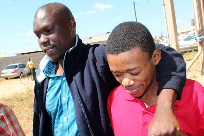 """Accused of having relations """"against the order of nature"""", James Mwape (R) is comforted by his relative after he was acquitted by the Kapiri Mposhi magistrate court on July 3, 2014 (AFP Photo/)"""