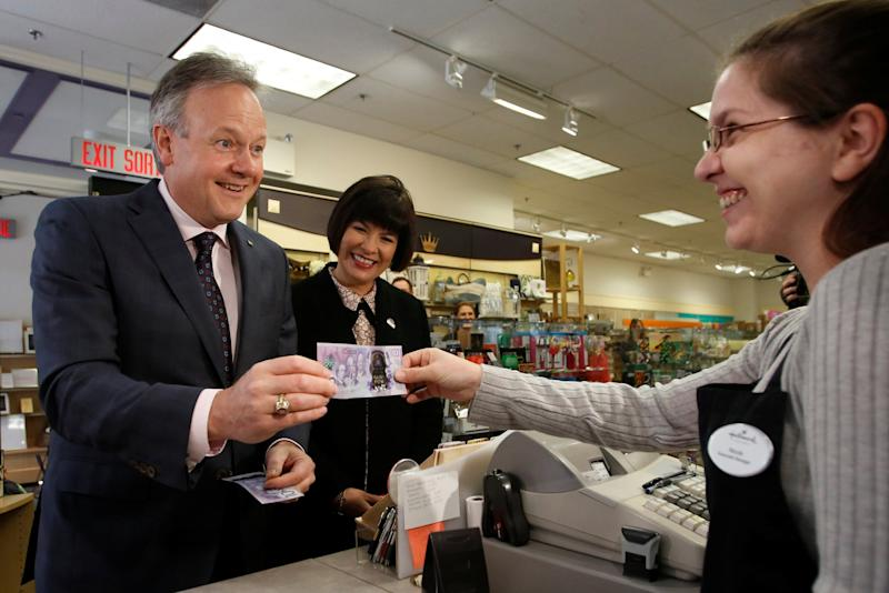 Bank of Canada Governor Stephen Poloz pays for an item with a commemorative $10 bank note celebrating the 150th anniversary of Canada's confederation during a photo opportunity at a store in Ottawa, Ontario, Canada June 1, 2017. (Reuters)