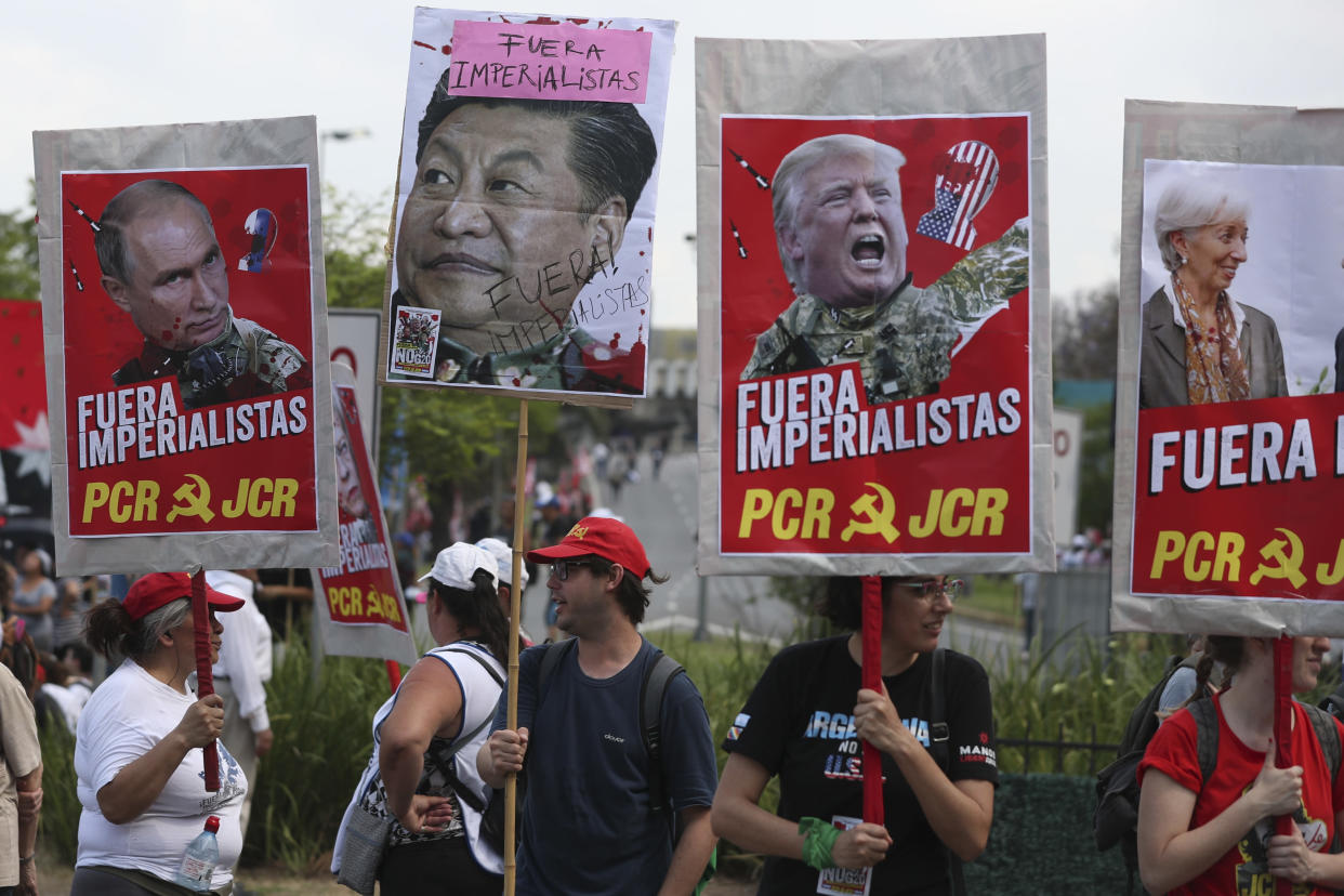 """Protesters with signs of the face of, from left, Russia's President Vladimir Putin, China's President Xi Jinping, President Donald Trump and IMF Managing Director Christine Lagarde, covered by the Spanish phrase """"Get out imperialists!,"""" march against the G20 summit being held in Buenos Aires, Argentina, Friday, Nov. 30, 2018. Leaders from the Group of 20 industrialized nations are meeting in Buenos Aires for two days starting today. (Photo: Martin Mejia/AP)"""