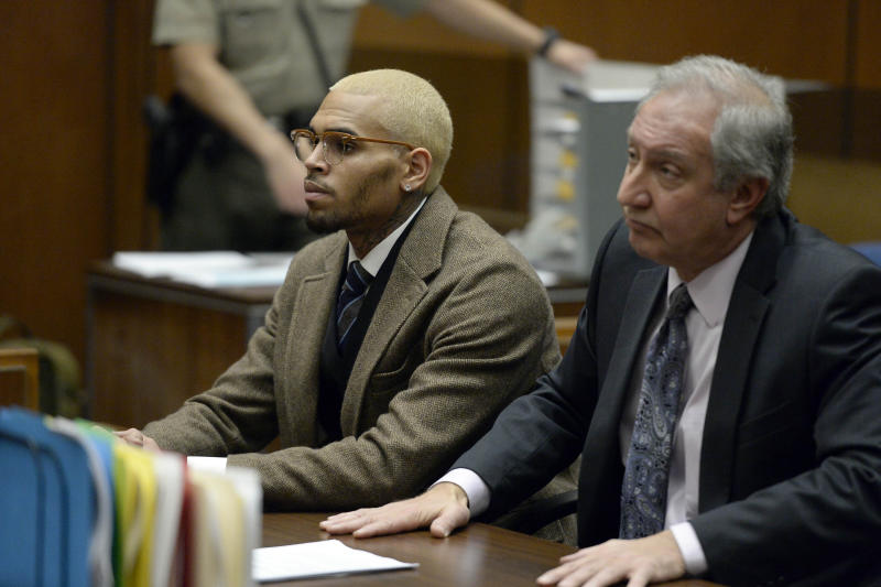R&B singer Chris Brown, left, appears in court with his attorney Mark Geragos during a probation violation hearing in which his probation was revoked by a Los Angeles Superior judge on Monday, Dec. 16, 2013, in Los Angeles. Superior Court Judge James R. Brandlin revoked Brown's probation after his recent arrest on suspicion of misdemeanor assault in Washington, D.C., but the ruling will not alter the singer's requirements to complete rehab and community labor for his 2009 attack on Rihanna. (AP Photo/Kevork Djansezian, Pool)