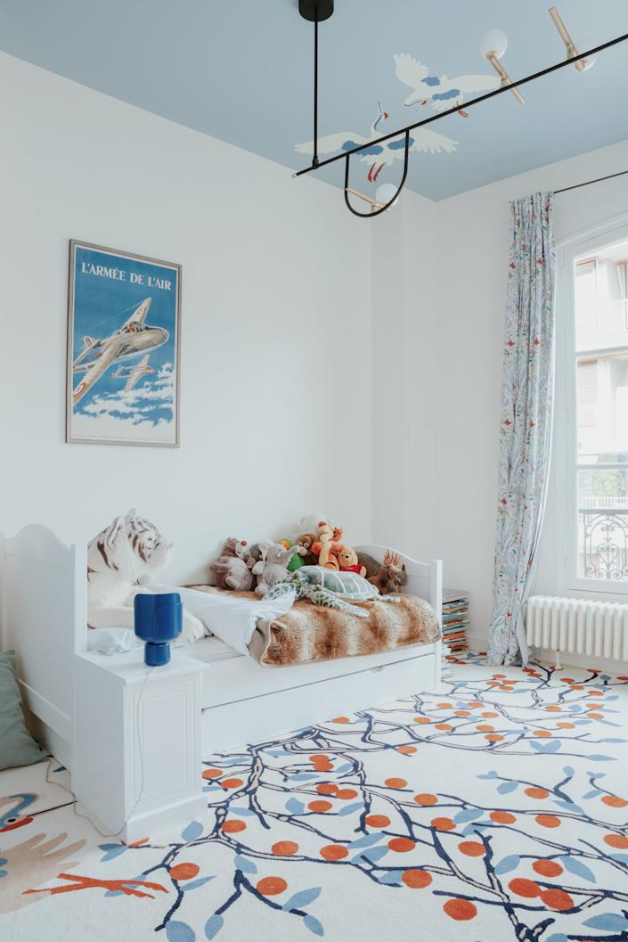 The ceiling in this part of the kids' room is painted in Lulworth Blue by Farrow & Ball and the curtains are by Little Cabari. The custom rug is by Marguerite Le Maire.