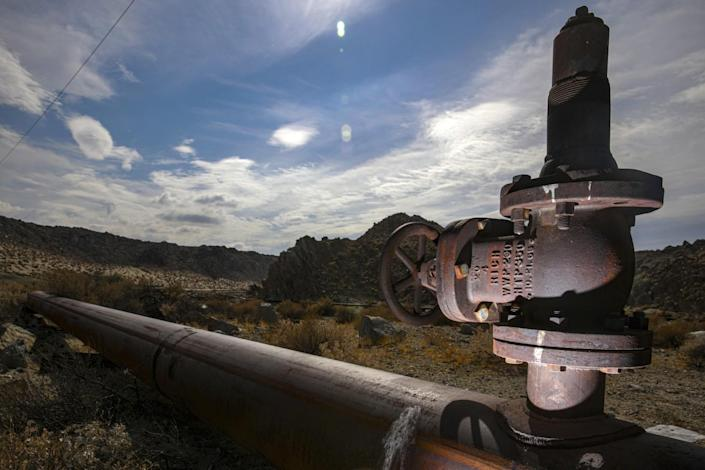 A closeup view of a valve on a water pipe that stretches away into a desert landscape