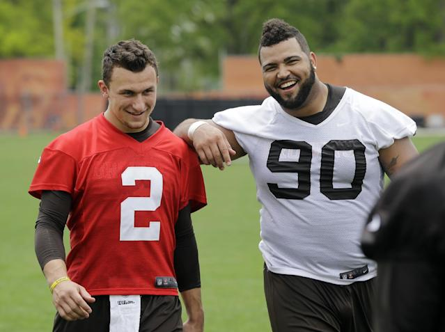 Cleveland Browns defensive end Billy Winn (90) jokes with rookie quarterback Johnny Manziel (2) after an off-season practice at the NFL football team's facility in Berea, Ohio Wednesday, May 21, 2014. (AP Photo/Mark Duncan)