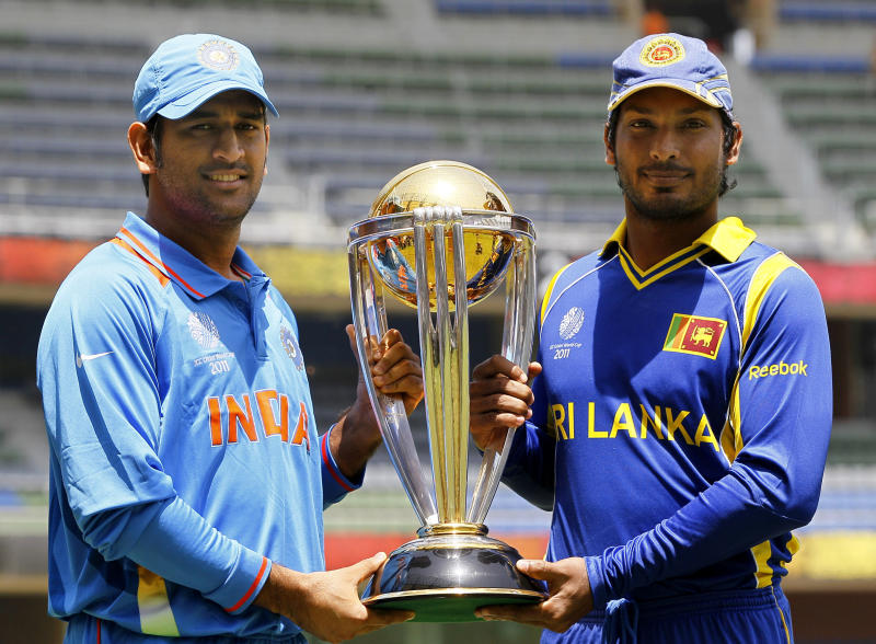 India's captain Mahendra Singh Dhoni, left, and Sri Lanka's captain Kumar Sangakkara pose for a photograph with the Cricket World Cup trophy in Mumbai, India, Friday, April 1, 2011. India will play Sri Lanka in the Cricket World Cup final in Mumbai on April 2. (AP Photo/Kirsty Wigglesworth)