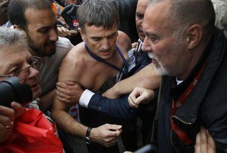 A shirtless Xavier Broseta (C) is evacuated by security after employees interrupted a meeting with representatives staff at the Air France headquarters building at the Charles de Gaulle International Airport in Roissy, near Paris, France, October 5, 2015. REUTERS/Jacky Naegelen
