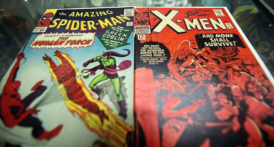 A Spider-Man comic book featuring the Human Torch and Green Goblin next to an X-Men comic book.