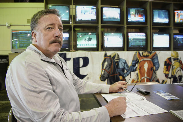 Joe Brown waits for the horses to race at Fonner Park in Grand Island, Neb., Saturday, March 14, 2020. Fonner was one of the few sporting venues in the country open to fans Saturday, unfortunately the races were called off due to dangerous track conditions following snowfall. (AP Photo/Nati Harnik)