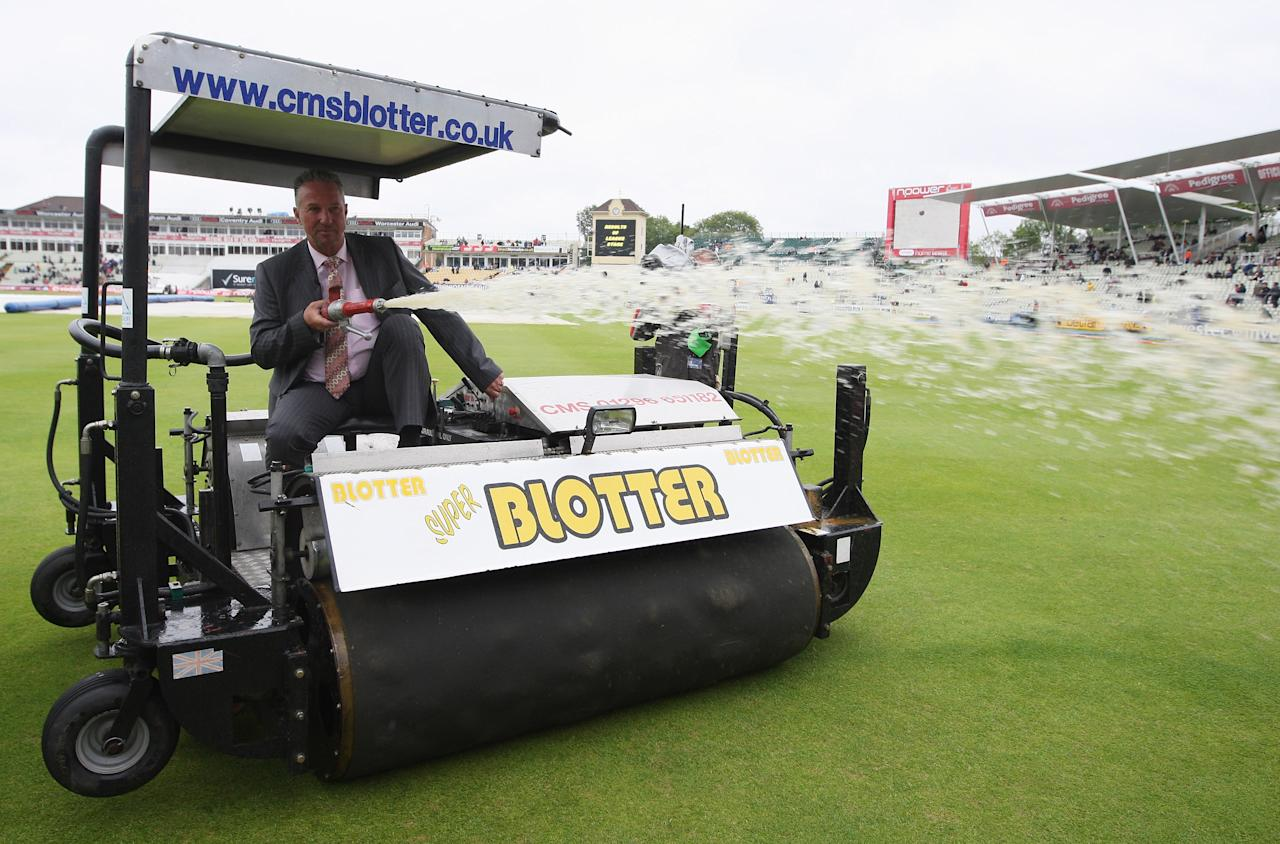 BIRMINGHAM, UNITED KINGDOM - AUGUST 01: Sky commentator Ian Botham sprays water over the boundary from the Blotter after rain during day three of the npower 3rd Ashes Test Match between England and Australia at Edgbaston on August 1, 2009 in Birmingham, England.  (Photo by Hamish Blair/Getty Images)