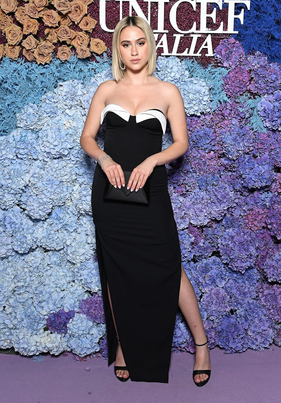 <p>wears a strapless gown with white accent at the neckline, with ankle-strap heels.</p>