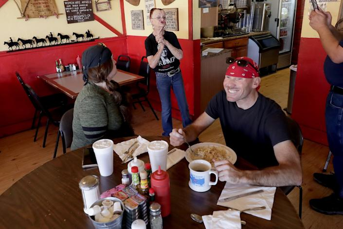 Customers cheer Debbie Thompson, owner of the Horseshoe Cafe in Wickenburg, Ariz.