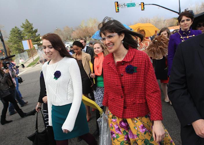 Hannah Wheelwright, left, and Kate Kelly, along with other Mormon women pushing the church to allow women in the priesthood, march to Temple Square during the two-day Mormon church conference Saturday, April 5, 2014, in Salt lake City. The church has asked the women to reconsider, and barred media from going on church property during the demonstration. Mormon officials allowed the women's group to demonstrate its displeasure for not being allowed in an all-male meeting, on church property but still didn't let them attend. (AP Photo/Rick Bowmer)