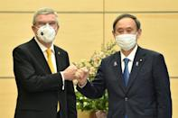 Japan's Prime Minister Yoshihide Suga (R) met International Olympic Committee president Thomas Bach (L) in Tokyo in November
