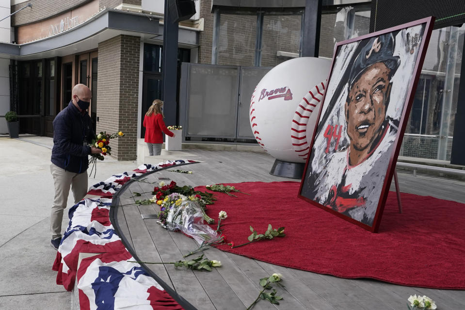 Atlanta Braves employees place flowers next to a portrait Atlanta Braves' Hank Aaron outside Truist Park, Friday, Jan. 22, 2021, in Atlanta. Aaron, who endured racist threats with stoic dignity during his pursuit of Babe Ruth but went on to break the career home run record in the pre-steroids era, died peacefully in his sleep early Friday. He was 86. (AP Photo/John Bazemore