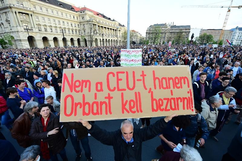 """Hungary's threat to close the Soros-founded Central European University (CEU) sparked mass protests in Budapest, with one demonstrator holding a placard that reads """"Don't close CEU, send Orban to jail"""" (AFP Photo/ATTILA KISBENEDEK)"""