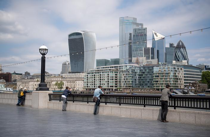 People observe social distancing as they look out at the view of the skyline of the City financial district from alongside Tower Bridge, London, following the introduction of measures to bring England out of lockdown. (Photo by Dominic Lipinski/PA Images via Getty Images)