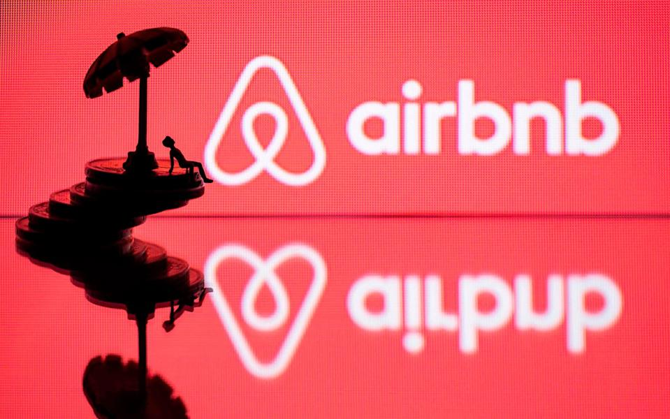 A toy umbrella and a figurine on coins asre seen next to the logo of rental website Airbnb