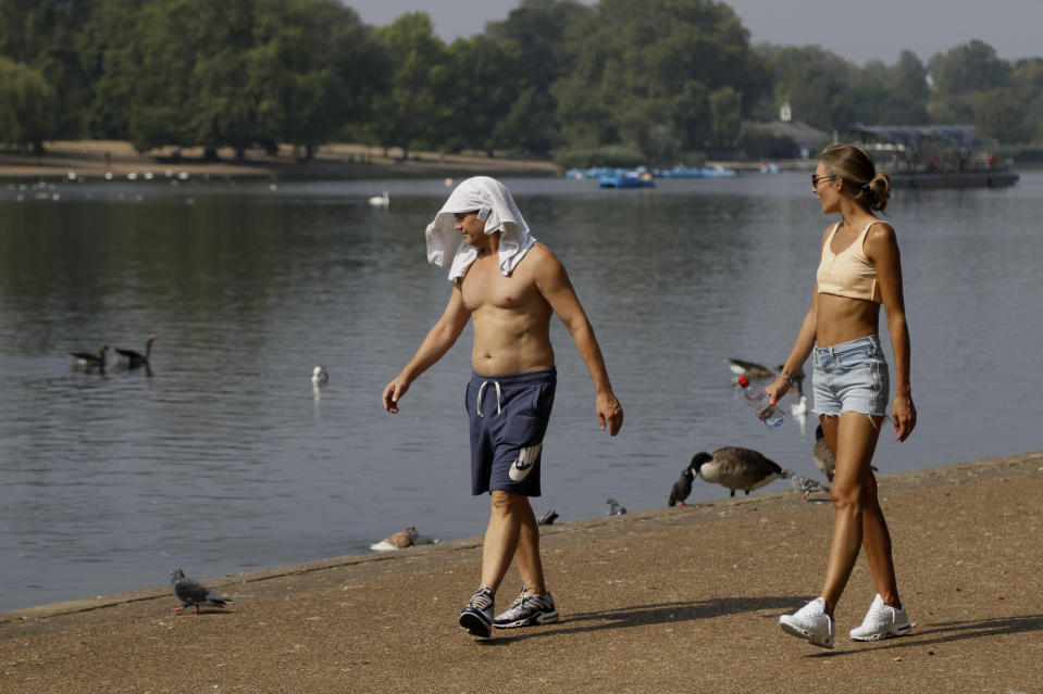 FILE - In this Wednesday, Aug. 12, 2020 file photo, a man keeps cool with a shirt over his head as he walks alongside The Serpentine in Hyde Park in London with high temperatures forecast again for many parts of England. (AP Photo/Kirsty Wigglesworth)