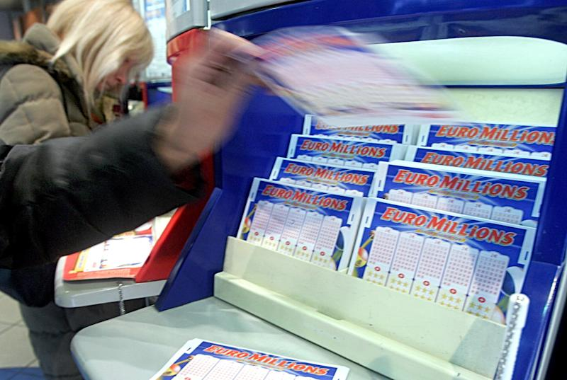 A customer picks up a Loto ticket in a Paris loto shop Friday Jan. 13, 2006. Thousands of players are buying Euromillion tickets hoping to win the 103 million Euros ($124,156,000) bonus on Friday's draw. (AP Photo/Remy de la Mauviniere)