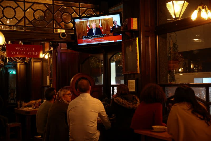 People watch Britain's Prime Minister Boris Johnson announce new lockdown measures inside a pub in Westminster, amid the coronavirus disease (COVID-19) outbreak, in London