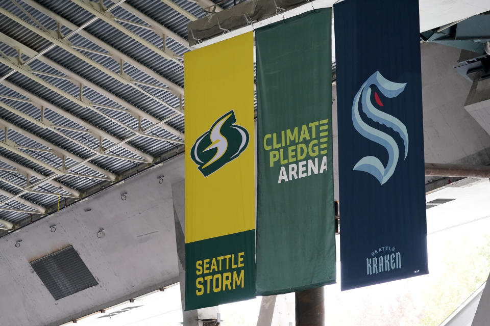 FILE - In this Oct. 7, 2020, file photo, banners for Seattle's Kraken NHL hockey team, right, and Storm WNBA basketball team hang alongside an arena banner during a media tour of construction on the arena in Seattle. The Buffalo Sabres won the NHL draft lottery and the expansion Kraken jumped up the order to take the No. 2 pick Wednesday night, June 2, 2021. (AP Photo/Elaine Thompson, File)