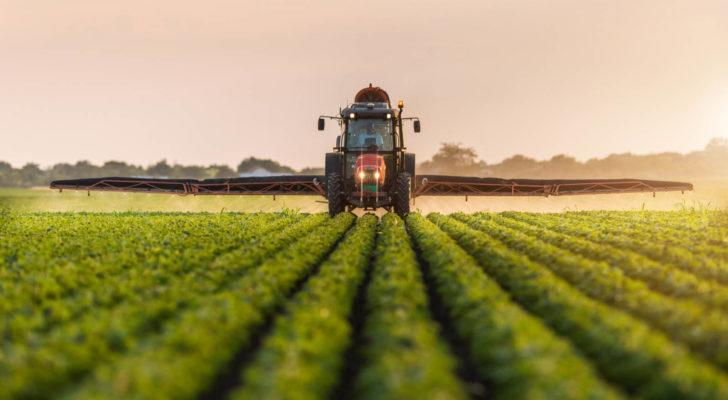 Tractor spraying pesticides on soybean field with sprayer