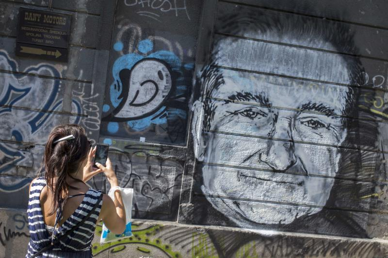 A woman takes a picture of a mural depicting late actor Robin Williams in Belgrade, August 13, 2014. The mural was drawn on a building in downtown Belgrade by an unknown artist on Tuesday. Oscar-winning actor and groundbreaking comedian Williams hanged himself with a belt in his Northern California home after he had sought treatment for depression, a coroner said on Tuesday, based on preliminary findings. REUTERS/Marko Djurica (SERBIA - Tags: ENTERTAINMENT OBITUARY)