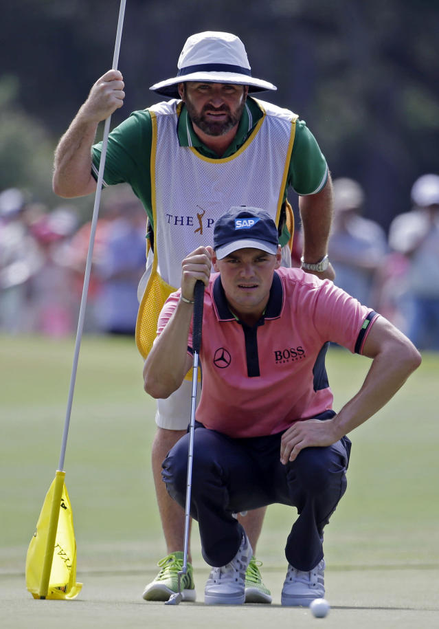 Martin Kaymer, bottom, of Germany, and his caddie Craig Connelly look at Kaymer's shot on the seventh green during the final round of The Players championship golf tournament at TPC Sawgrass, Sunday, May 11, 2014, in Ponte Vedra Beach, Fla. (AP Photo/Lynne Sladky)