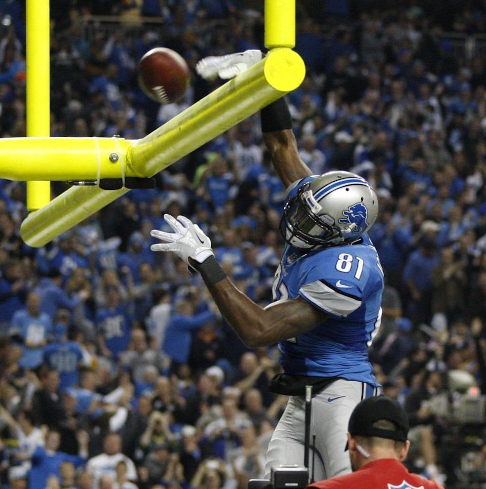 Calvin Johnson dunks the ball over the goal post after his third-quarter touchdown against the Green Bay Packers in Detroit on Nov. 28, 2013.
