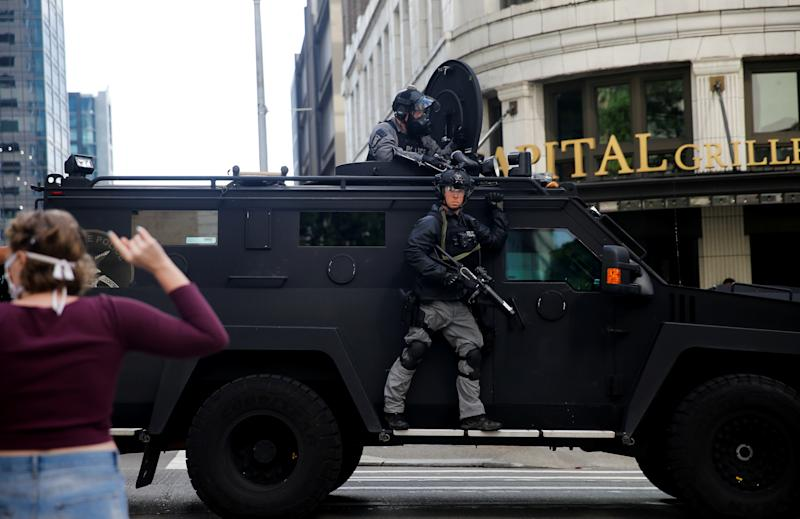 Seattle police drive by protesters in an armored vehicle during aprotest against the death in Minneapolis police custody of George Floyd, in Seattle, Washington, U.S. May 31, 2020. REUTERS/Lindsey Wasson