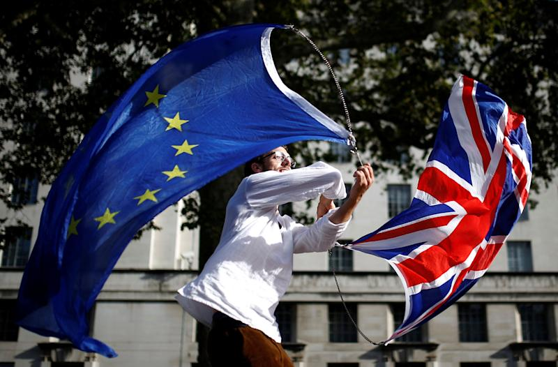 A EU supporter waves flags while other demonstrators march as parliament sits on a Saturday for the first time since the 1982 Falklands War, to discuss Brexit in London, Britain, October 19, 2019. REUTERS/Henry Nicholls (Photo: Henry Nicholls / Reuters)