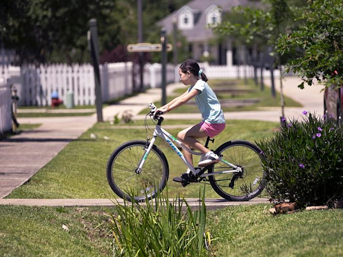 Juliet Daly rides her bike outside her home in Covington, La on April 30, 2020.